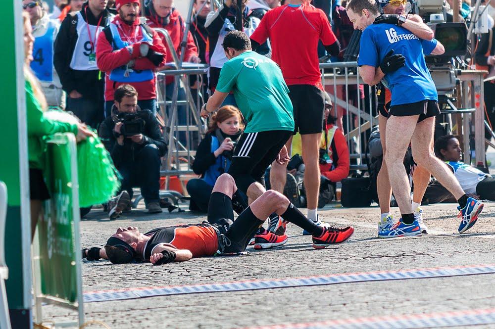 Coureurs étendus par terre à l'arrivée du Marathon